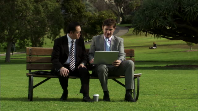 ms, two businessmen working on laptop in park, sydney, australia - 座る点の映像素材/bロール