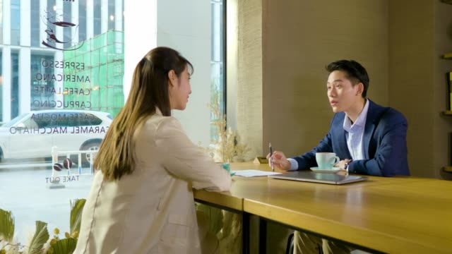 WS DS MS Two businesspeople discussing documents in cafe, Beijing, China