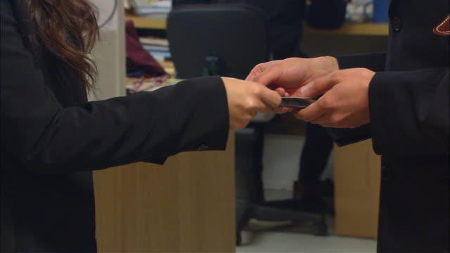cu, two businesspeople exchanging business cards in office, close-up of hands - exchanging stock videos & royalty-free footage
