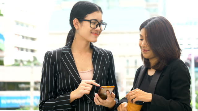 Two Businesswoman talking and drinking coffee outdoors
