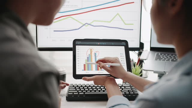two businesswoman using digital tablet analyzing business data financial analysts see charts and graphs on digital tablet - two people stock videos & royalty-free footage