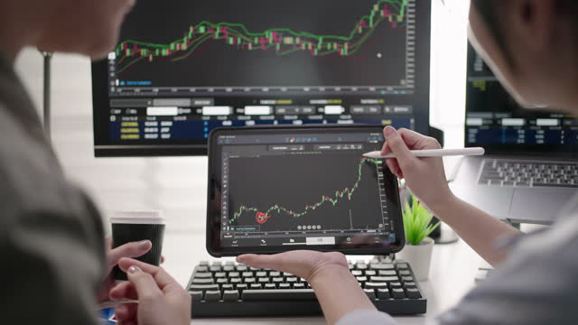 two businesswoman using digital tablet for analyzing stock market data graph - stock price stock videos & royalty-free footage