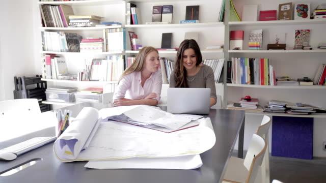 vídeos y material grabado en eventos de stock de dos empresaria usando computadora portátil - arquitecta