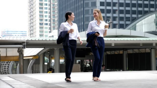 two businesswoman walk and discuss business in a break time with coffee at central city business centre downtown , slow motion - fare una pausa video stock e b–roll