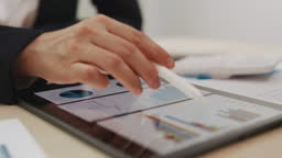 Two businesswomen analyzing Data graphs on digital tablet in an office