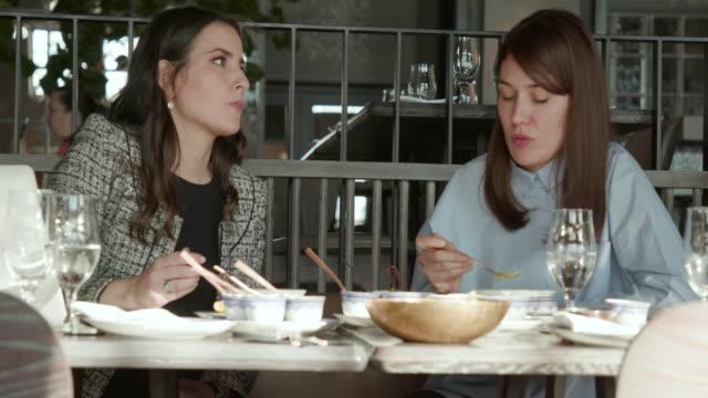 vidéos et rushes de deux femmes d'affaires, manger la soupe au restaurant - goûter