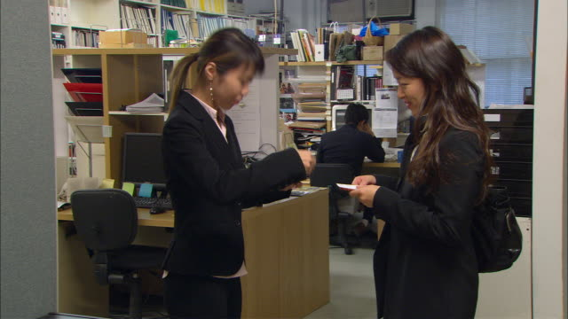 vídeos de stock e filmes b-roll de cu, two businesswomen exchanging business cards in office, man working in background - 2007