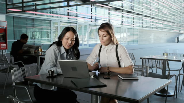 MS Two businesswomen sitting in cafeteria and using laptop, Los Angeles, California, USA