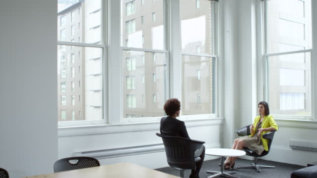 MS Two businesswomen sitting in discussion in corner conference area in office