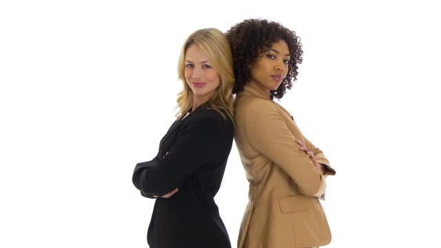 two businesswomen standing back to back looking at camera - stillstehen stock-videos und b-roll-filmmaterial