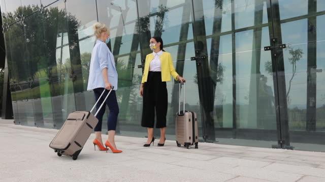 stockvideo's en b-roll-footage met twee zakenvrouwen die voor bureaugebouw spreken - hoge hakken