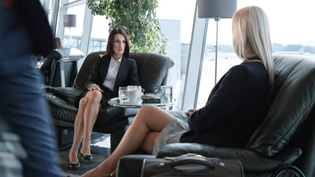 ds two businesswomen talking in the business lounge at the airport - cross legged stock videos & royalty-free footage