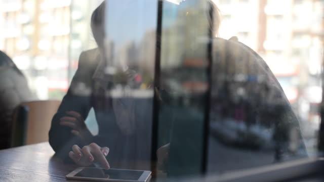two businesswomen using a computer and digital tablet at coffee shop discussing project - europäischer abstammung stock-videos und b-roll-filmmaterial
