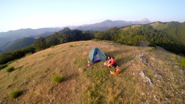 vídeos y material grabado en eventos de stock de two campers seated near a tent with a dog in a mountain - camping