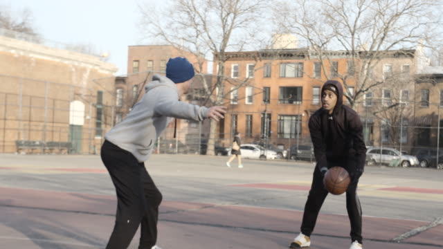 Two candid, real people play basketball on a cold Brooklyn, New York City morning - 4k
