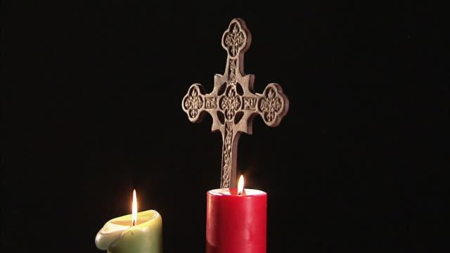 two candles burn around a rotating cross. - kreuz religiöser gegenstand stock-videos und b-roll-filmmaterial
