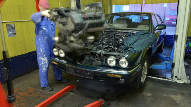 two car mechanics replace an engine - wiederaufbau stock-videos und b-roll-filmmaterial