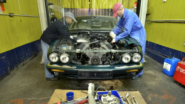 two car mechanics replace an engine - rebuilding stock videos and b-roll footage
