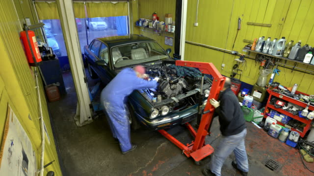 two car mechanics replace an engine - car engine stock videos & royalty-free footage