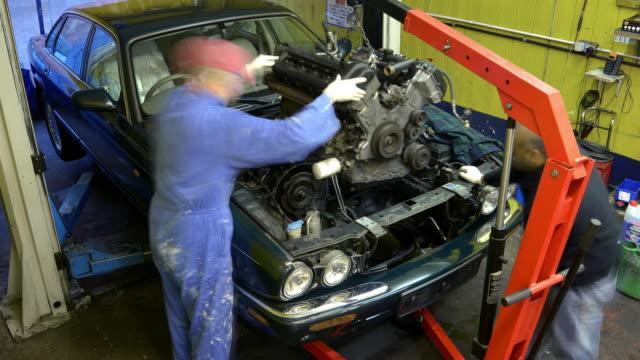 two car mechanics replace an engine - motore video stock e b–roll
