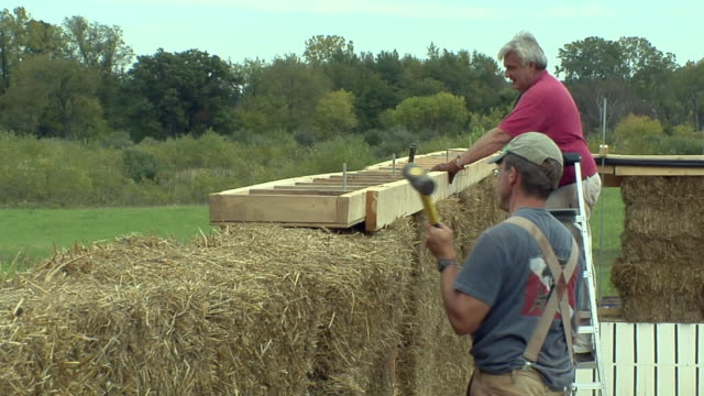 MS Two carpenters working atop wall of house built with bales of straw, Grass Lake, Michigan, USA