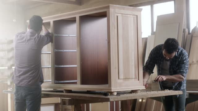 Two carpenters working together on big piece of furniture at carpenter shop