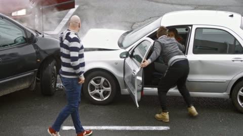 vídeos y material grabado en eventos de stock de dos coches chocan y los pasos de pasajero masculino hacia fuera y mujer piloto en otro coche recibe ayuda - accidente de tráfico