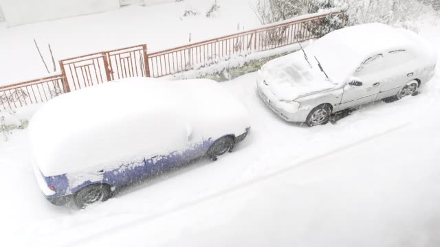 Two cars covered with snow during the snowstorm