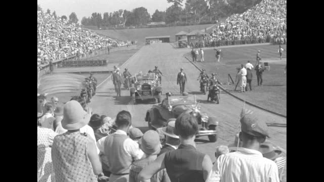 two cars driving along track in stadium, second car carrying herbert hoover and wife lou, policemen on motorcycles escorting cars, crowd in stands /... - nomination stock videos & royalty-free footage