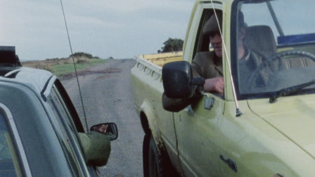 1983 montage two cars meeting on road and stopping to visit, with doctor in one providing a consultation and prescription for a possible broken finger to the patient in the other / porlock, somerset, england - ポーロック点の映像素材/bロール