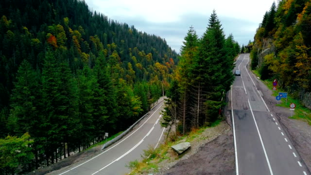 Two cars moving on differnt sides of hairpin curve. Aerial view