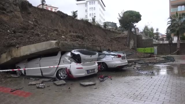 Two cars parked at a parking lot of a residential building were damaged when a retaining wall collapsed after a heavy rainfall in Alanya district of...