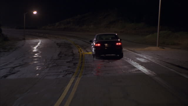 two cars swerve to miss each other on a wet road at night. - near miss stock videos and b-roll footage