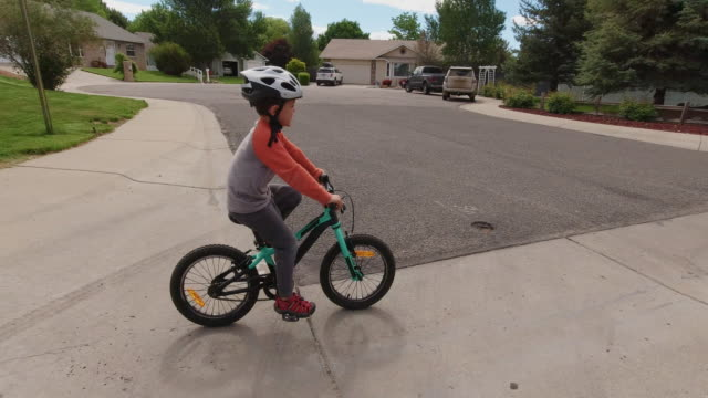 two caucasian boys (five years-old and four years-old) wearing bike helmets cross the street as they ride their bikes through a residential neighborhood under a partly cloudy sky - cycling helmet stock videos & royalty-free footage