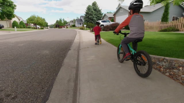 vídeos de stock e filmes b-roll de two caucasian boys (five years-old and four years-old) wearing bike helmets ride their bikes through a residential neighborhood under a partly cloudy sky - capacete de ciclismo