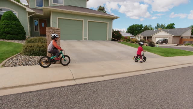 two caucasian boys (five years-old and four years-old) wearing bike helmets ride their bikes through a residential neighborhood under a partly cloudy sky - riding stock videos & royalty-free footage