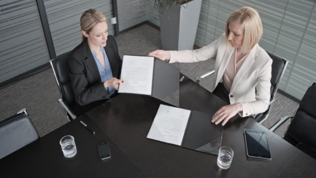 CS Two Caucasian businesswomen signing a contract in the conference room and shaking hands