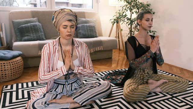 zwei kaukasische ruhige frauen meditieren in lotus-position zu hause - spiritualität stock-videos und b-roll-filmmaterial
