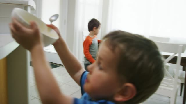two caucasian little boys (three and five years old) place their dirty dishes on the counter of a kitchen - lavori domestici video stock e b–roll