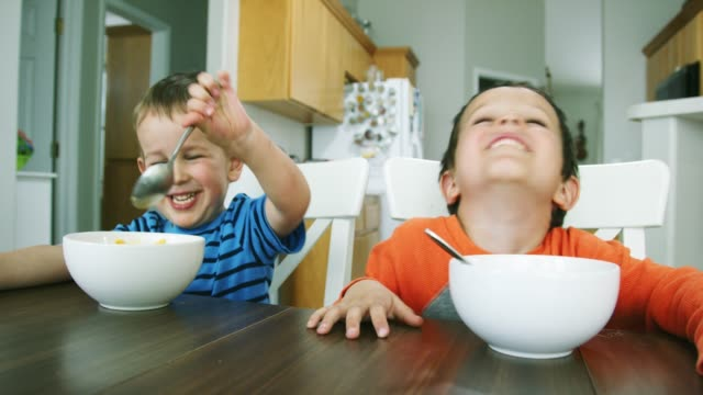 two caucasian little boys (three and five years-old) sit at a kitchen table and eat bowls of macaroni and cheese pasta while laughing and acting silly - table stock videos & royalty-free footage