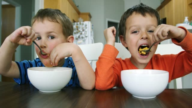 two caucasian little boys (three and five years-old) sit at a kitchen table and eat bowls of macaroni and cheese pasta - 4 5 years stock videos & royalty-free footage