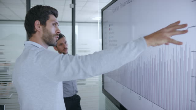 two caucasian male colleagues discussing a financial graph shown on large screen in the meeting room - leadership stock videos & royalty-free footage