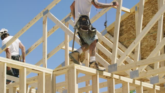 two caucasian male construction workers in their forties walk along wooden roof trusses while framing a house on a clear, sunny day - roof beam stock videos & royalty-free footage