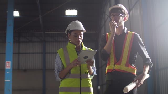 vídeos de stock, filmes e b-roll de dois funcionários de armazém caucasiano usando tablet digital para verificar estoque na fábrica - usar laptop
