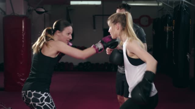 two caucasian women boxing with a trainer - boxing women's stock videos & royalty-free footage