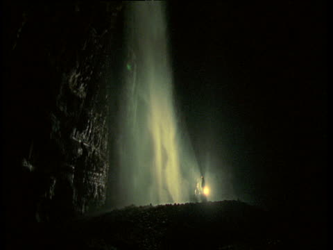 vídeos y material grabado en eventos de stock de two cavers stand next to lit up cave waterfall in gaping gill hole, yorkshire - yorkshire