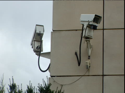 Two CCTV cameras on side of building one rotating London