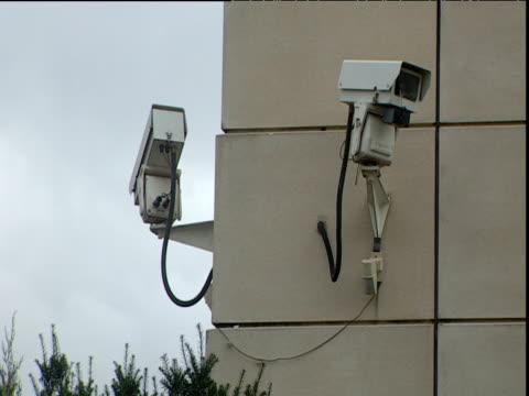 two cctv cameras on side of building one rotating london - telecamera di sorveglianza video stock e b–roll