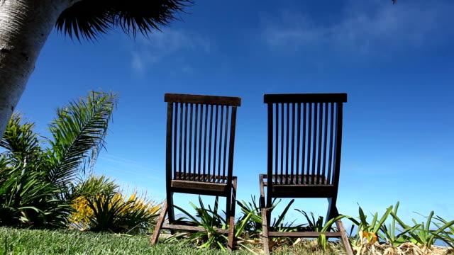 Zwei Liegestühle unter Palmen
