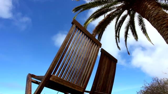vídeos de stock, filmes e b-roll de duas cadeiras sob palmeiras - cadeira dobrável
